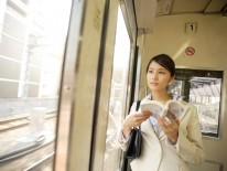 Business woman looking at an outer view from inside of train