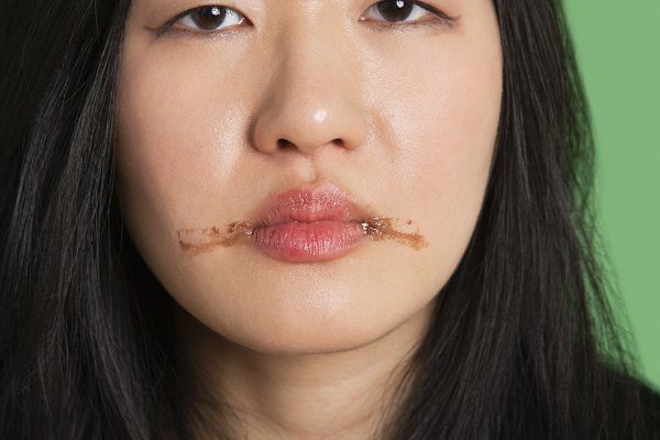 Portrait of a young woman with chocolate stains around her lips
