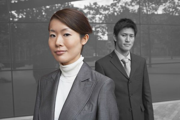 Portrait of young businesswoman with coworker outside office building